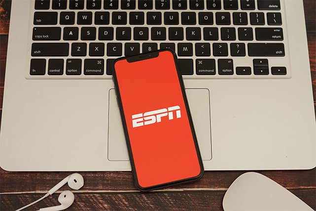 An image featuring a laptop and earphones on the bottom, while in the middle there is a mobile phone that has ESPN+ opened on it