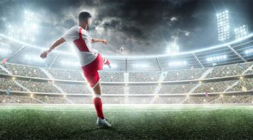 An image featuring a football/soccer player shooting a football/soccer ball on a stadium representing football/soccer league