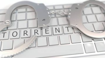 An image featuring a keyboard with handcuffs on top of it that says torrent representing illegal torrenting