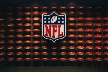 An image featuring footballs in the background with the NFL logo in the middle representing the national football league