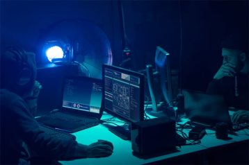 An image featuring 2 people represented as hackers and using their computers