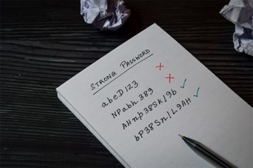 An image featuring a notebook with weak and strong passwords on it