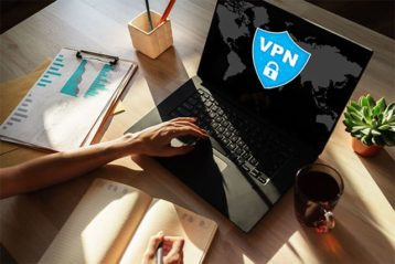 An image featuring a person using his laptop that has a VPN logo on it