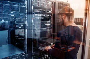 An image featuring a person using his laptop in a server room representing a modern ISP (Internet Service Provider)