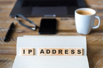 An image featuring IP Address text with blocks on top of a notebook with a laptop, coffee, phone and glasses in the background