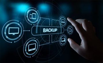 An image featuring a person holding out their finger on a cool drawn system that says backup on it representing data backup