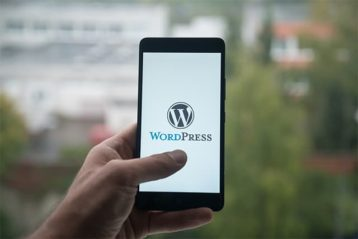 An image featuring a person holding their phone outside and has opened WordPress
