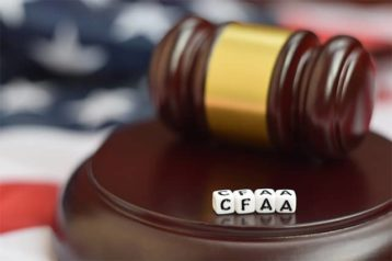 An image featuring a gavel with dices that say CFAA representing the computer fraud and abuse act of 1986 concept