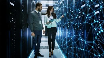 An image featuring two people walking in a server room