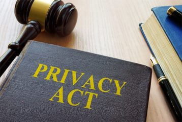 An image featuring a book that says privacy act on it with a gavel next to it representing privacy act rules
