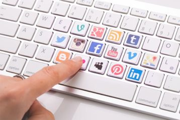 An image featuring a keyboard that has a lot of social media logos on the keys representing social media activities