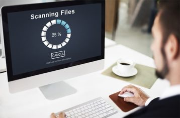 An image featuring a person using his MacBook and is scanning his files for malware