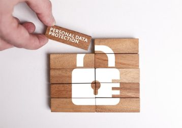 An image featuring a person holding a wooden rectangle that says personal data protection on it representing data privacy