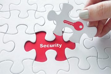 An image featuring a person holding a puzzle that has a red lock key on it and is putting it on top of security representing data security concept