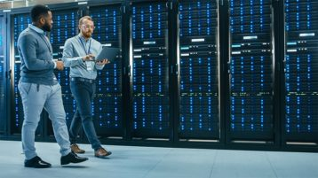 An image featuring two people walking in a server room representing managed hosting concept