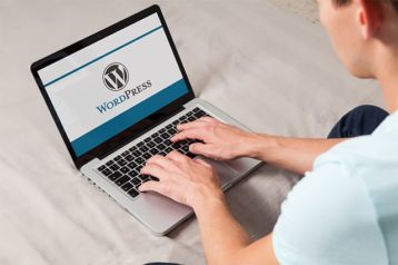 An image featuring a person using his laptop and is logging in in his WordPress website