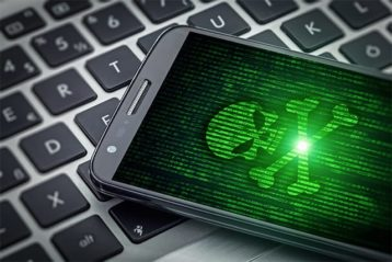 An image featuring a laptop that has a phone on top of it with a green malware logo representing malware concept