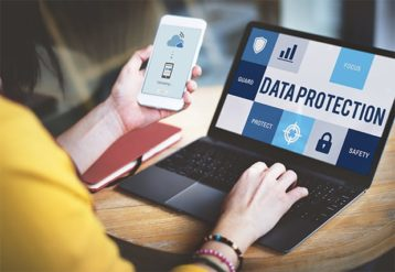 An image featuring a person using her phone and laptop that says data protection on it representing digital space protection concept