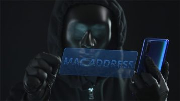 An image featuring a person wearing a hoodie and a mask representing a hacker while holding a phone and has a virtual screen in front of him that says mac address