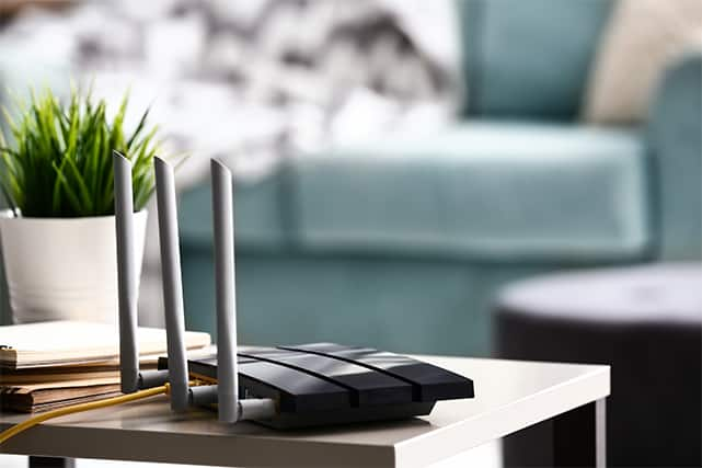 An image featuring a router in a living room with a plant next to it