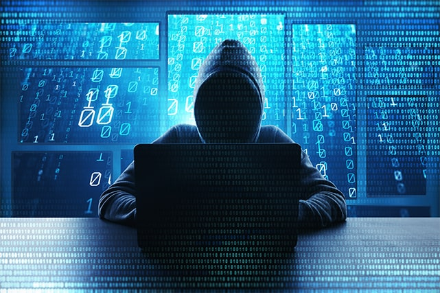 An image featuring a person wearing a dark hoodie and using his laptop representing a hacker with a hacker-ish background concept